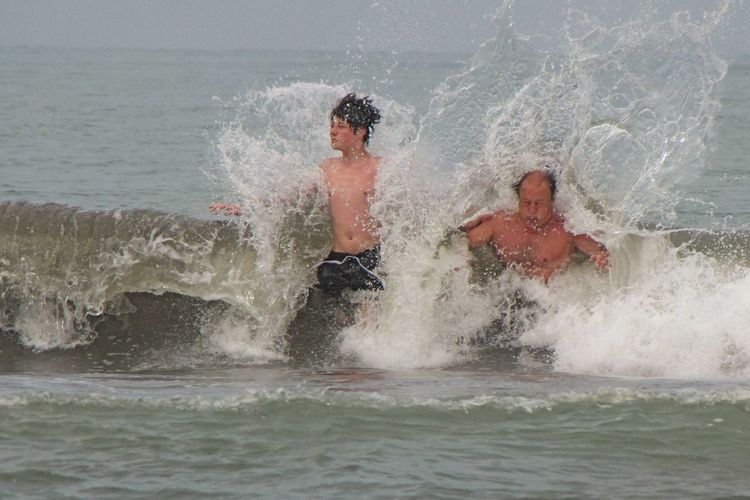 Father with son swimming in sea
