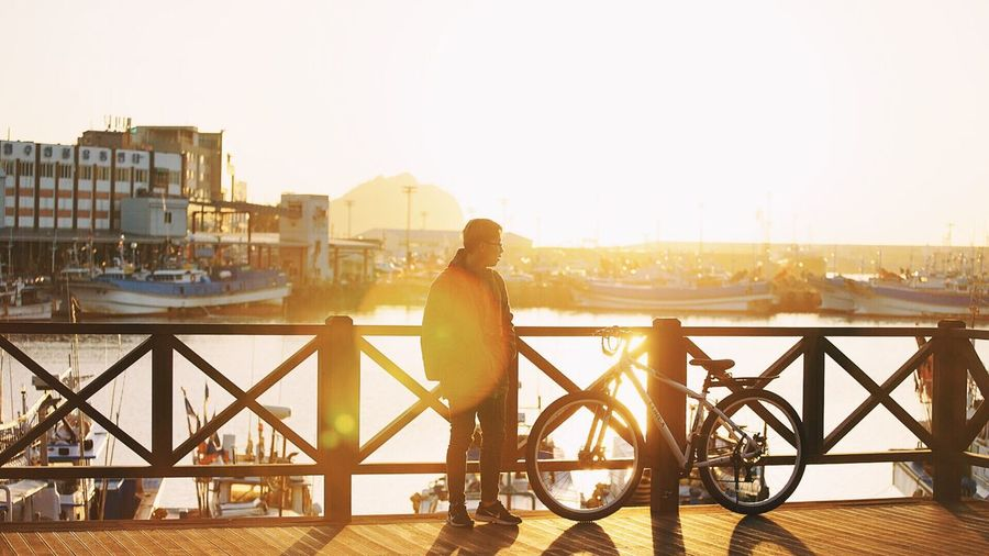 Man with bicycle on bridge in city
