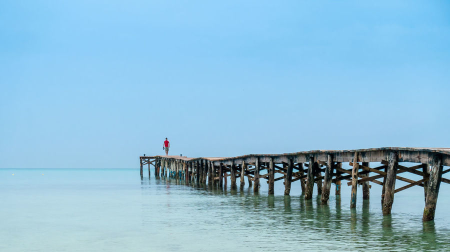 Man Walking On Pier Over Sea Against Clear Blue Sky