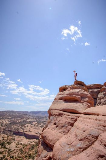 Man standing on rock formations against sky