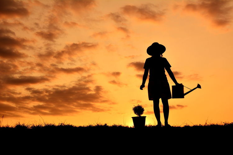 Woman standing on field with potted plant and watering can