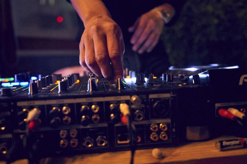 Cropped image of dj mixing sound at nightclub