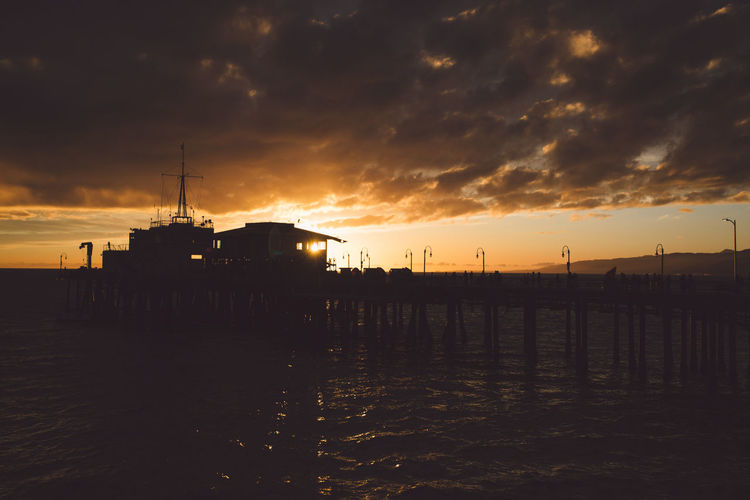 Silhouette Santa Monica Pier Over Sea Against Cloudy Sky During Sunset