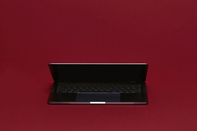 Reflective Laptop Computer on a Red Background Computer Studio Shot Indoors  Red Technology Connection Copy Space No People Colored Background Communication Wireless Technology Computer Equipment Still Life Close-up Red Background High Angle View Laptop Single Object Table Cut Out Apple Backgrounds Monitor