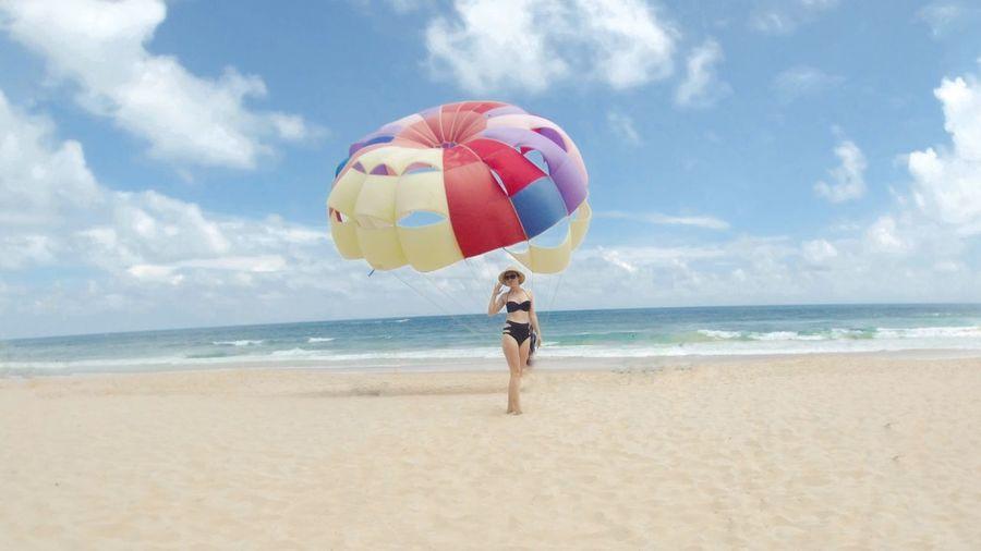 Woman walking against parasol at beach