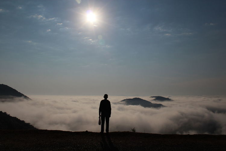 Rear view of silhouette man standing on landscape against sky