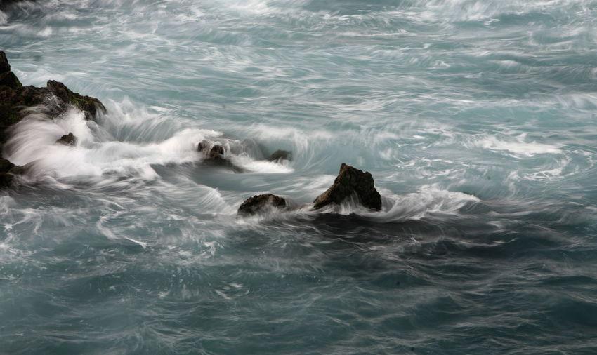 Waves Crashing On Rocks In Sea