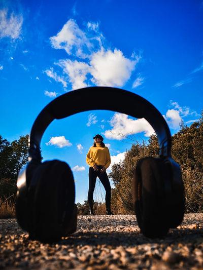 Woman standing on road seen through headphones