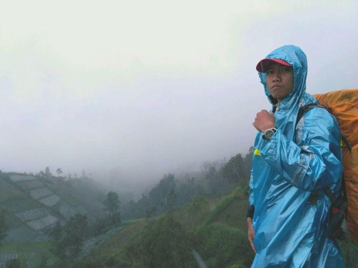 Portrait of hiker wearing raincoat against sky