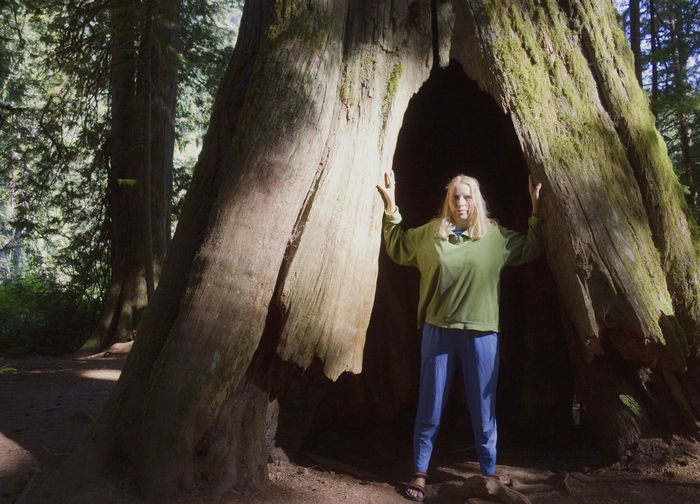 Woman in front of giant Douglas Fir – Pseudotsuga menziesii - Cathedral Grove, MacMillan Provincial Park, Vancouver Island, British Columbia, Canada Arms Raised Bark British Columbia Canada Cathedral Grove Douglas Fir Environment Exploring Fir Tree Front View Full Length Giant Hole Hollow Hollow Tree MacMillan Provincial Park Majestic One Woman Only Pseudotsuga Menziesii Scale  Standing Tree Tree Trunk Vancouver Island Woman