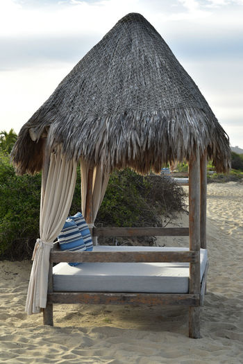 luxury glamping tropical beach bed with palm thatched palapa roof Beach Life Bed Absence Beach Beauty In Nature Costal Day Glamping Idyllic Lounge Chair Nature No People Outdoors Relaxation Relaxation Beside The Sea Roof Sand Scenics - Nature Seat Sky Thatched Roof Tranquil Scene Tranquility Umbrella Water