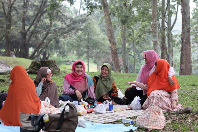 Muslimah women having picnic outdoors Group Of People Women Sitting Adult Togetherness Tree Nature Day People Leisure Activity Females Mid Adult Casual Clothing Lifestyles Outdoors Land Plant Muslim Muslimah Picnic Garden Traveler