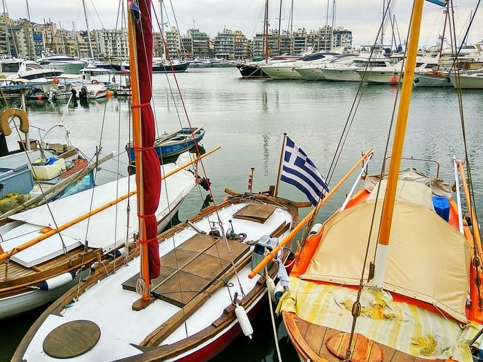 Nautical Vessel Boats Boats And Water Tranquility Reflection In The Water Sea Smartphonephotography Sea Life Classic Marina No People Nature Day Transportation High Angle View Reflection Water Classic Boat Greek Flag Smartphone Photography Tranquil Scene Cloud - Sky Cloudy Day Paint The Town Yellow