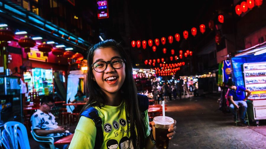 Real People Incidental People One Person Night Front View Illuminated Focus On Foreground Standing Text Portrait Smiling Enjoyment Lifestyles Leisure Activity Long Hair Headshot Outdoors Looking At Camera Young Adult Women The Street Photographer - 2017 EyeEm Awards