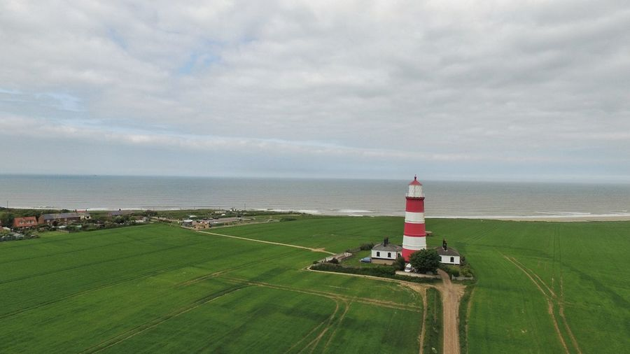 Water Sea Lighthouse Beach Agriculture Safety Sky Grass Building Exterior Horizon Over Water Coastline Tranquil Scene Farmland Calm Growth Countryside Shore Tranquility Coast Coastal Feature