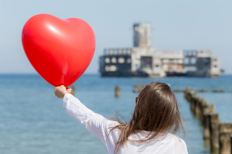 Close-Up Of Hand Holding Balloon Against Calm Sea
