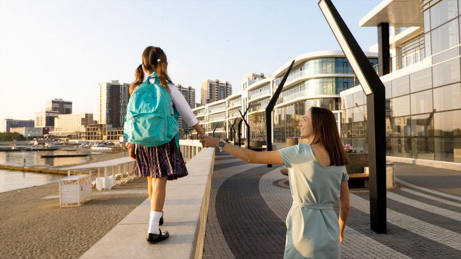 Woman walking on footpath against buildings in city