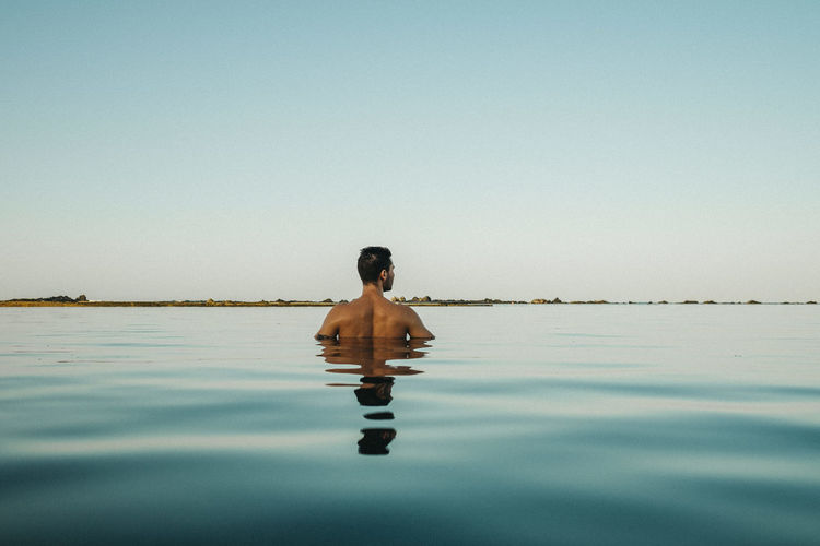 Rear view of man swimming in infinity pool against clear sky