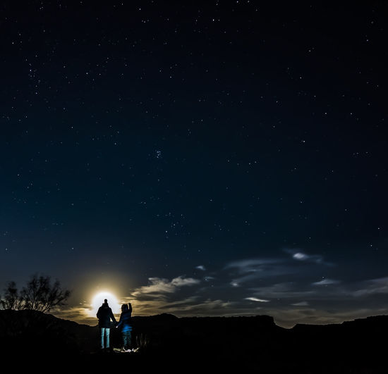 Rear view of couple standing on field against star field at night