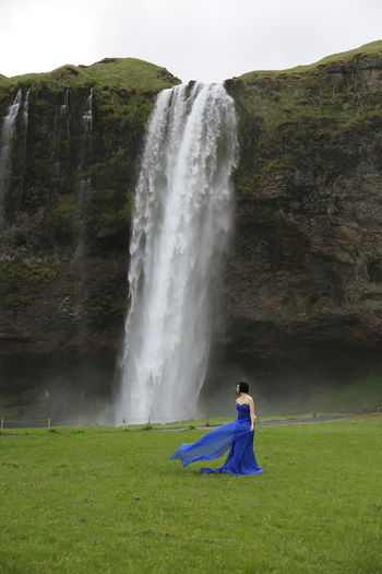 Beautiful woman standing by waterfall against sky