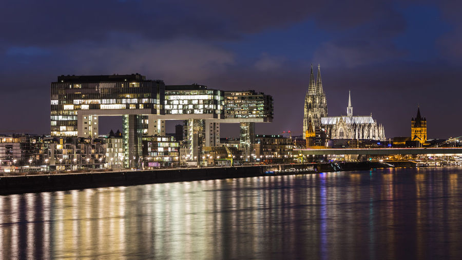 """Cologne Cathedral and the illuminated Kranhäuser (""""Crane houses"""") and reflections in the river rhine after sunset in Cologne, Germany Building Exterior Architecture Built Structure City Illuminated Water Night Cityscape Reflection Travel Destinations Waterfront No People River Cologne Köln Kölner Dom Cologne Cathedral Kranhäuser Kranhaus Famous Place Travel Long Exposure Hafen Dom Cologne"""