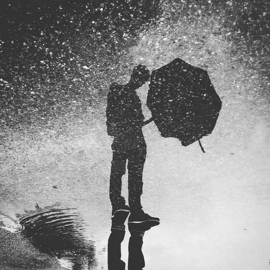 Upside down image of man standing with reflection in puddle on street