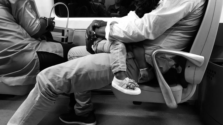 Low section of men sitting in bus