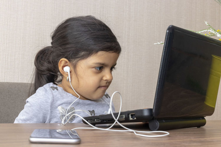 Girl using laptop on table at home