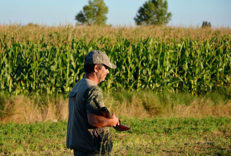 Man with weapon standing on agricultural field