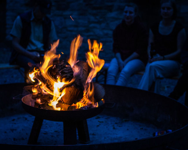 Fire with people sitting in background at night