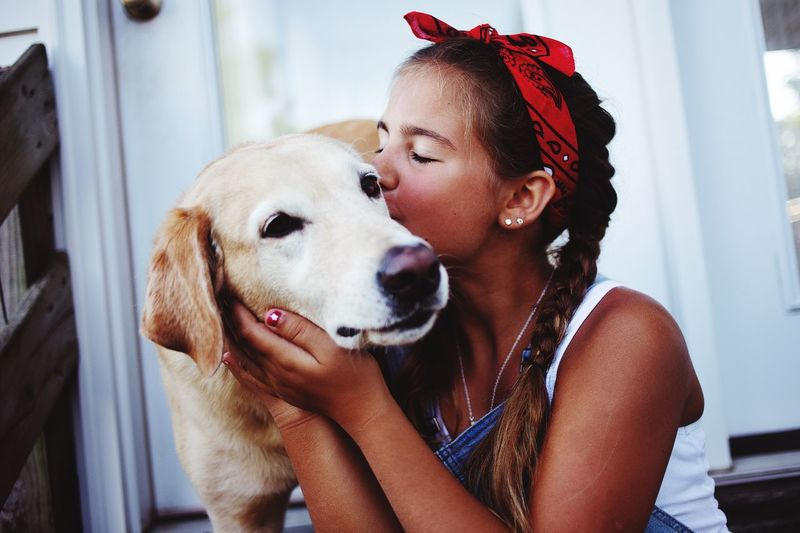 Girl kissing dog at home