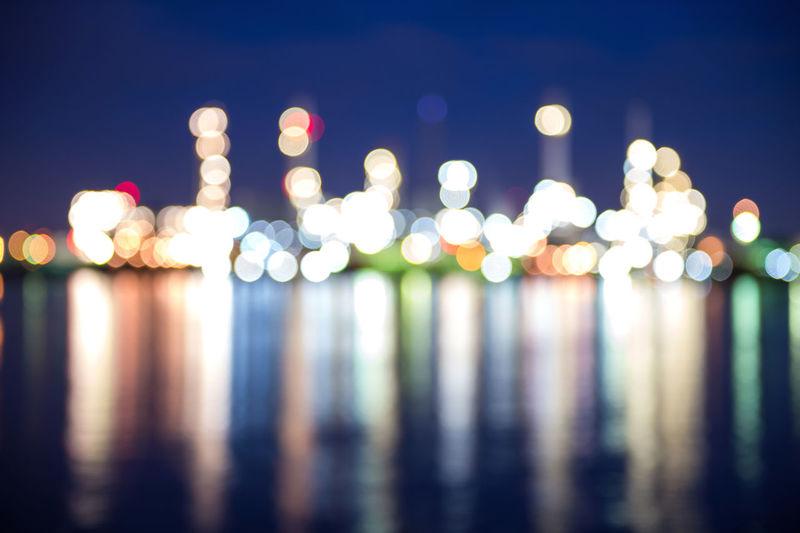 Defocused image of illuminated lights reflecting on lake at night