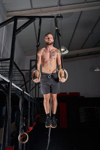 Full length of shirtless man sitting on ceiling