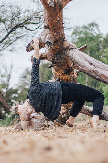 Low section of person on tree trunk on field