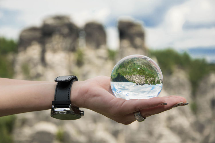 Hand holding crystal ball with upside down image of bastei