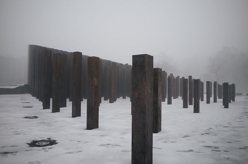 Wooden posts on snow covered landscape against sky