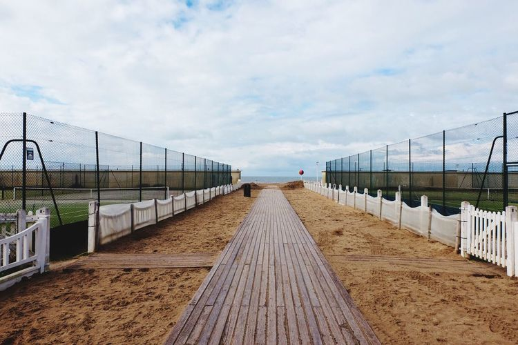 Boardwalk amidst playing field at beach against cloudy sky