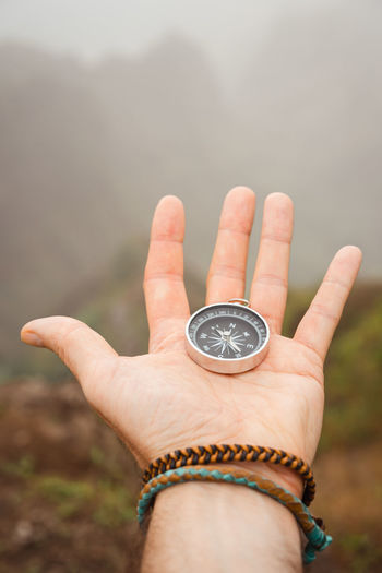 Close-Up Of Person Hand Holding Navigational Compass Over Field