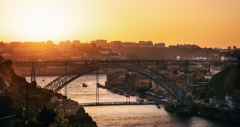 Dom luis bridge over river in city against orange sky