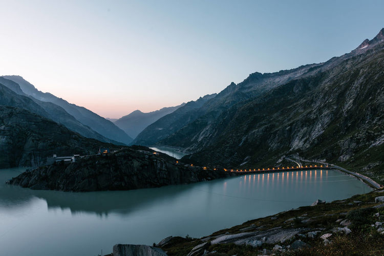 Scenic view of dam by mountains during sunset