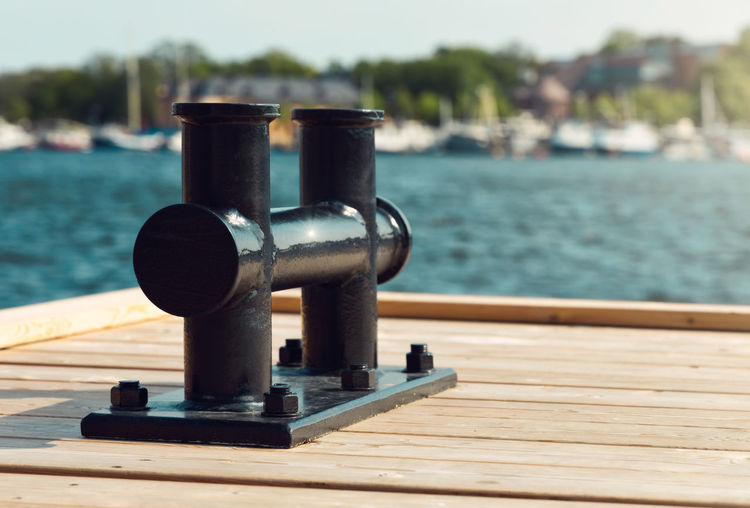 Close-up of pier on table against sea