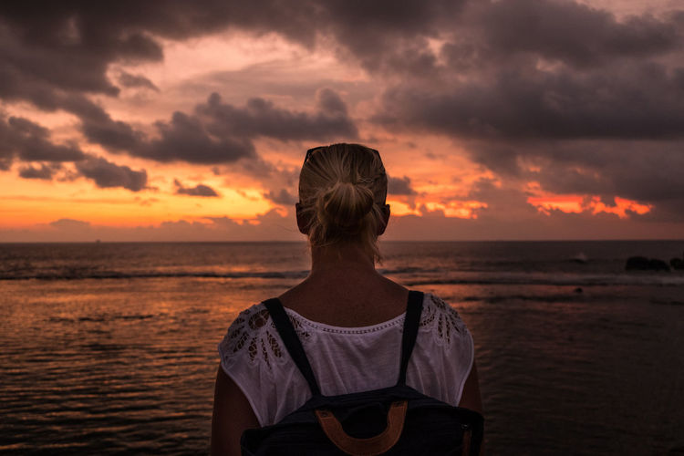 Rear view of woman looking at sea against cloudy sky during sunset