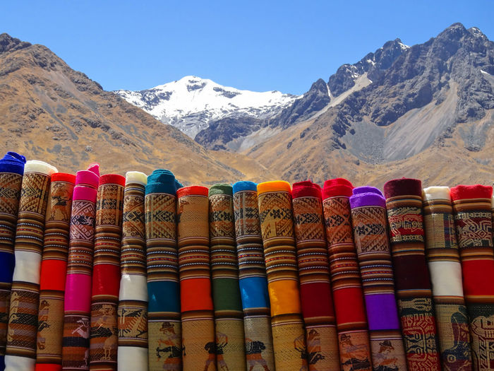 Stack of multi colored chairs against mountains