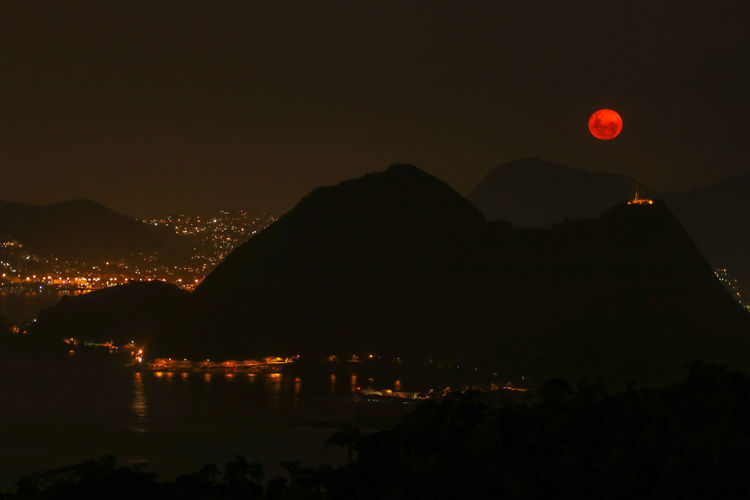 red moon in río de Janeiro Mountain Sea Rio De Janeiro Red Moon Cityscape City Mountain Illuminated Nightlife Moon Cityscape Astronomy Sky Full Moon Moonlight Eclipse Solar Eclipse Astrology