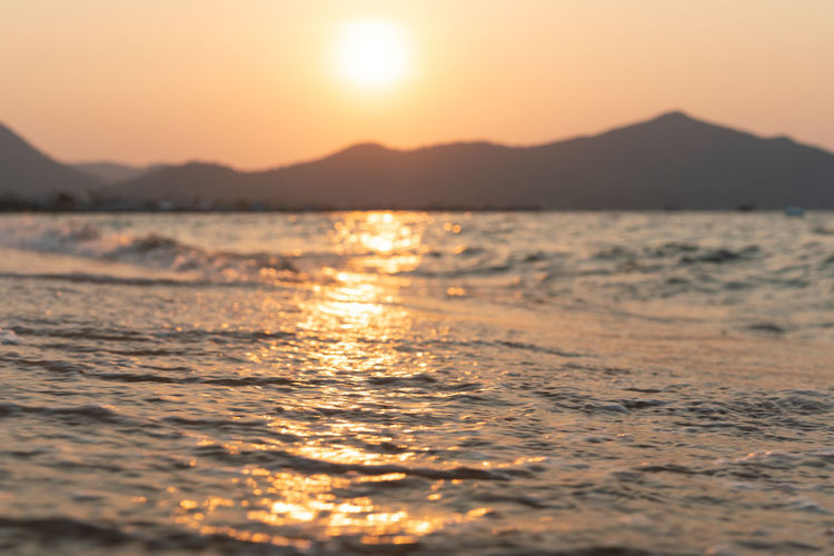 Water Sky Sunset Beauty In Nature Mountain Sea Reflection Scenics - Nature Beach Nature Sun Tranquility Sunlight No People Wave Outdoors Tranquil Scene Peaceful Calm Water Calm Sea Distant Mountains Sun Reflection On Water Golden Hour Coastline Landscape Coast