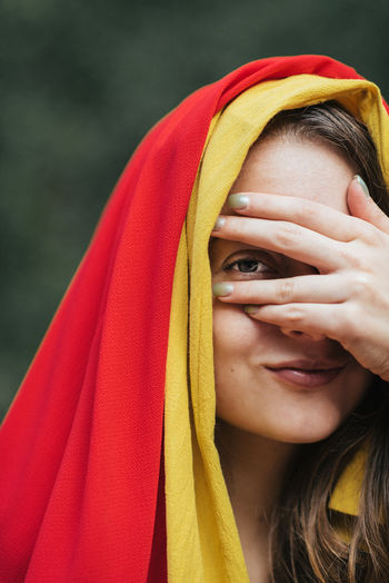 Portrait of young woman with hands covering eyes