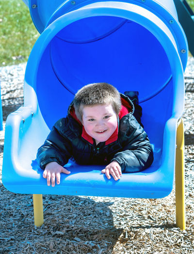 Cute Boy Wearing Blue Jacket Playing In Playground