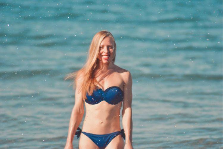 Beautiful young woman in bikini standing in sea