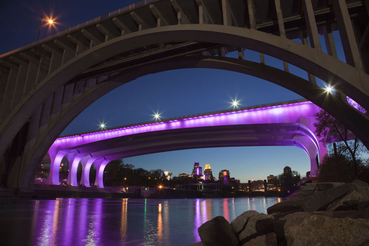 The 35W bridge over the Mississippi River in Minneapolis illuminated with purple lights in honor of the death of Prince 35 W Death Lights Low Angle View Memorial Minneapolis, Minnesota Mississippi River Posthumous Reflection Arch Architecture Bridge - Man Made Structure City Honor Illuminated Night Prince  Purple River Rocks Water Editorial