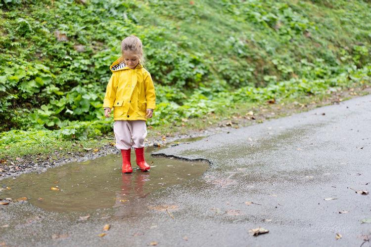 Rear view of girl walking on wet road